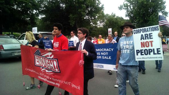 John Bonifaz, President of Free Speech for People, marches beside Jonah Minkoff-Zern of Public Citizen holding up a sign that says, 'Enough! Corporations are NOT people. Money is NOT speech.'